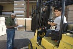 Travailleur conduisant Forktruck et écriture d'homme supérieur sur le presse-papiers Photo stock