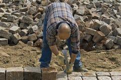 Travailleur : constructeur de route étendant des pavés ronds Image libre de droits