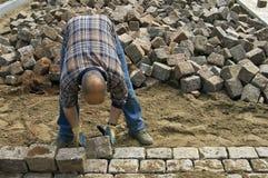 Travailleur : constructeur de route étendant des pavés ronds Photos stock