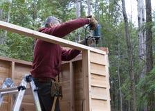 Travailleur construisant le hangar de stockage de DIY Photos stock