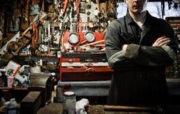 Travailleur croisé par bras dans un hangar et un bon nombre d'accrocher d'outils Photos stock