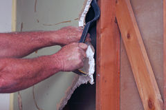 Travailleur déchirant outre de la cloison sèche avec l'outil Photo libre de droits