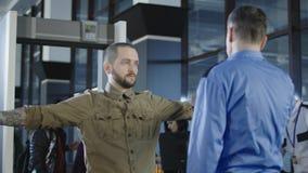 Travailleur d'aéroport vérifiant le passager avec le détecteur de métaux  images stock