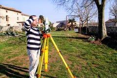 Travailleur d'arpenteur faisant la mesure dans le jardin, station totale Images stock