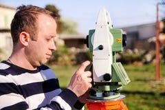 Travailleur d'arpenteur faisant la mesure dans le jardin, station totale Photo libre de droits