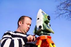 Travailleur d'arpenteur faisant la mesure dans le jardin, station totale Image libre de droits