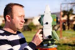 Travailleur d'arpenteur faisant la mesure dans le jardin, station totale Photographie stock