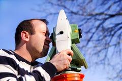 Travailleur d'arpenteur faisant la mesure dans le jardin, station totale Images libres de droits