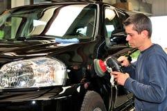 Travailleur polissant une voiture. Photos stock