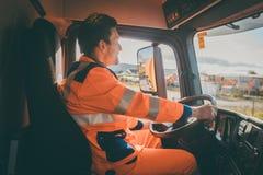 Travailleur d'enlèvement de déchets conduisant un camion à benne basculante photo libre de droits