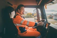 Travailleur d'enl?vement de d?chets conduisant un camion ? benne basculante images libres de droits