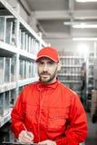 Travailleur d'entrepôt avec le presse-papiers dans le stockage photos stock