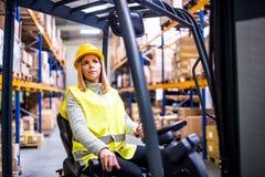 Travailleur d'entrepôt de femme avec le chariot élévateur image libre de droits