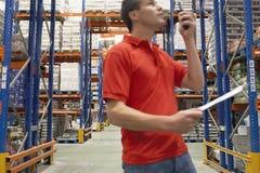 Travailleur d'entrepôt à l'aide du talkie-walkie Images stock