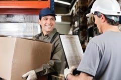 Travailleur d'entrepôt regardant le surveillant avec Photos stock
