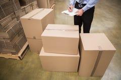 Travailleur d'entrepôt vérifiant sa liste sur le presse-papiers photo stock