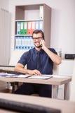 Travailleur d'entreprise de sourire dans la chemise bleue et lien parlant sur le pH Images stock