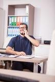 Travailleur d'entreprise de sourire dans la chemise bleue et lien parlant sur le pH Photographie stock libre de droits