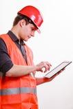 Travailleur d'homme dans le casque antichoc de gilet de sécurité utilisant le comprimé Photo libre de droits