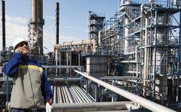 Travailleur d'huile à l'intérieur de grande raffinerie chimique Image libre de droits
