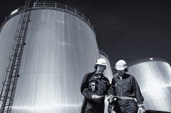 Travailleur d'huile avec la raffinerie et les réservoirs de carburant Photos stock