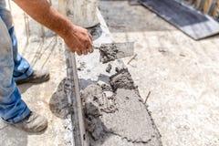 Travailleur d'industrie du bâtiment à l'aide d'un couteau de mastic et nivelant le béton sur les piliers concrets Photographie stock libre de droits
