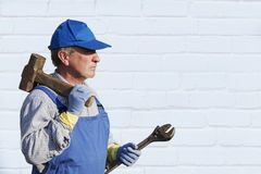 Travailleur dans des combinaisons bleues avec un marteau de forgeron et une clé Regard sérieux Contre un mur de briques blanc End Images libres de droits