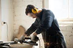 Travailleur dans des vêtements protecteurs fonctionnant dans l'atelier photo stock