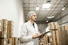 Travailleur dans l'entrepôt pour l'emballage alimentaire Photographie stock libre de droits