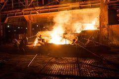 Travailleur dans l'industrie sidérurgique en versant les scories titaniques liquides du four à arc électrique Photos stock
