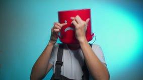 Travailleur dans l'uniforme avec le seau rouge sur son chef triste banque de vidéos
