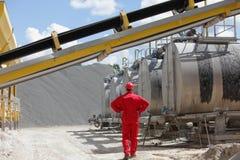 Travailleur dans l'uniforme rouge aux réservoirs avec l'asphalte images libres de droits