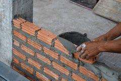 Travailleur dans la fin du maçon industriel installant les briques et la brique de ciment de mortier photos libres de droits