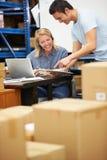 Travailleur dans le casque d'entrepôt et l'ordinateur portable de port d'utilisation Photos stock