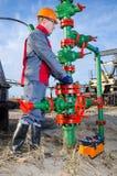 Travailleur dans le gisement de pétrole réparant la tête de puits Images stock