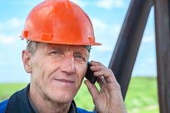 Travailleur dans le masque orange invitant le téléphone Photo stock