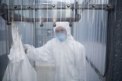 Travailleur dans le masque protecteur et costume derrière le mur en plastique au laboratoire Image libre de droits
