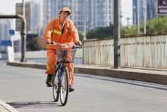 Travailleur dans les cycles oranges dans Pékin du centre, Chine Image stock