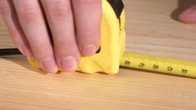 Travailleur de charpentier employant, roulette mesurant, dessus banque de vidéos