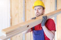 Travailleur de charpentier tenant des conseils Photo libre de droits