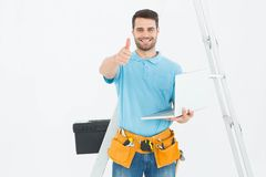 Travailleur de Construciton avec l'ordinateur portable faisant des gestes des pouces  Images libres de droits