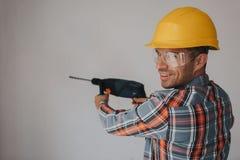 Travailleur de constructeur avec l'équipement faisant le trou dans le mur au chantier de construction Images stock