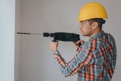 Travailleur de constructeur avec l'équipement faisant le trou dans le mur au chantier de construction Photos libres de droits