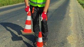 Travailleur de construction de routes avec des cônes du trafic sur la route banque de vidéos