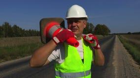 Travailleur de construction de routes avec deux cônes du trafic sur l'épaule banque de vidéos