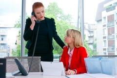 Travailleur de deux collègues dans le bureau avec l'ordinateur Photographie stock libre de droits