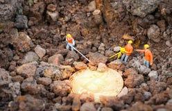 Travailleur de figurines extrayant Bitcoins d'or sur le sol de creusement de la terre profondément/le concept de extraction bitco photographie stock