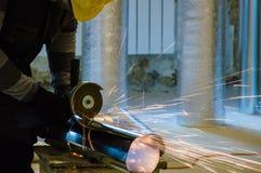 Travailleur de la CAHT coupant la canalisation métallique avec la broyeur d'angle moderne images libres de droits