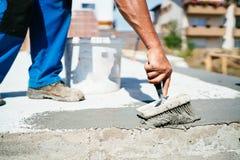 Travailleur de la construction à l'aide de la brosse et de l'amorce pour la maison de imperméabilisation utilisant des matériaux  photo libre de droits
