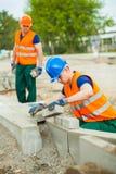Travailleur de la construction étendant des pavés ronds Photographie stock